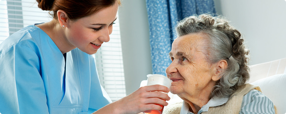 caregiver giving water to elderly patient