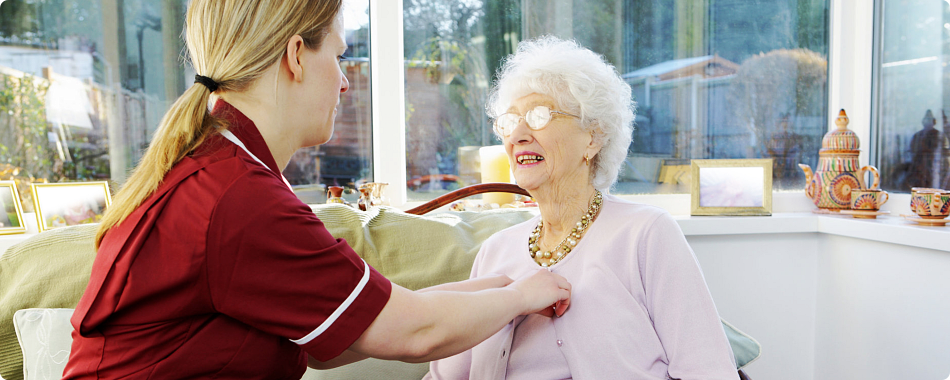 caregiver fixing the shirt of elderly patient