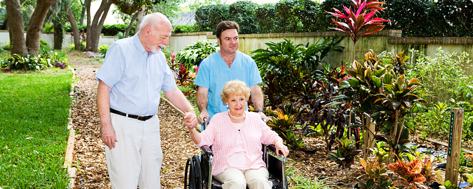 caregiver and elderly patients taking a stroll