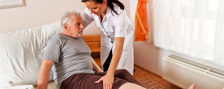 caregiver helping elderly patient to stand