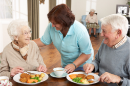 caregiver with elderly patients eating